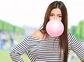 Portrait Of A Young Woman Blowing Bubblegum at a park