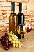 composition of wine and grapes on table on brick wall background