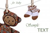 Clothesline with handcrafted fabric teddy bear and baby booties on white background with copy space.