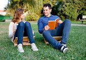Young Couple Reading A Book In The Park
