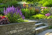 stock photo of stone house  - Natural stone landscaping in home garden with steps and flowerbeds - JPG
