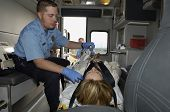 foto of stretcher  - Male ambulance worker taking pulse of patient lying on stretcher - JPG