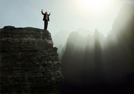 foto of ecstacy  - Businessman standing with arms raised in elation on the top of a mountain peak - JPG