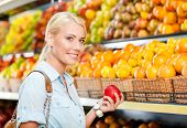 Girl at the shopping center choosing fruits and vegetables hands fresh red apple