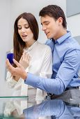 Male presents engagement ring to his woman at jeweler's shop. Concept of wealth and luxurious life