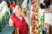 Senior man in Santa hat selecting Christmas ornaments at store
