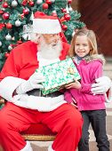 Happy girl taking present from Santa Claus against Christmas tree