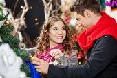 Happy young couple looking at each other while shopping for Christmas tree in store