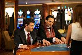 Two young cheerful men behind table in a casino