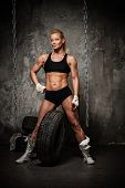 Beautiful muscular bodybuilder woman posing against tyres and chains