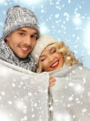 christmas, x-mas, winter, happiness concept - family couple under warm blanket