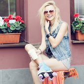 picture of roller-derby  - Young pretty blonde woman in roller skates having fun - JPG