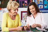 stock photo of thread-making  - Two Women Sewing Quilt Together - JPG