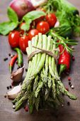 Fresh green asparagus bunch and vegetables on wooden board