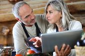 Senior couple in home kitchen looking at tablet