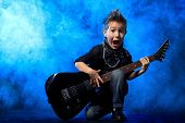 Cool little boy posing with electric guitar like a rock singer.