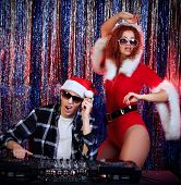 DJ man mixing up some Christmas cheer with attractive Snow Maiden. Disco lights in the background.