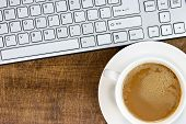 Keyboard And Coffee Cup On The Wooden Desk