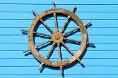 stock photo of ship steering wheel  - Large ship steering wheel on the side of a seafood restuarant - JPG