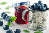 stock photo of jar jelly  - Jar of blueberry jam in a glass jar and fresh blueberries in an old metal cup on white wooden vintage background with green leaves - JPG