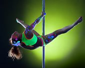 Muscular woman with neon makeup dancing on pole