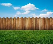 stock photo of farm landscape  - a wooden fence at the green grass - JPG