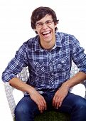 Portrait of laughing young man in glasses sitting on chair isolated on white background