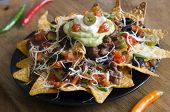 stock photo of nachos  - Spicy Nachos with beef chilli peppers sour cream and guacamole - JPG