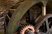 pic of water-mill  - Enclosed water mill wheel workings with ancient metal and wooden cog system part of industrial heritage - JPG