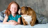 girl with her pet bulldog in bed