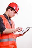 Man Worker In Safety Vest And Hard Hat Using Tablet