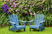 A pair of wooden Adirondack chairs in the summer garden.