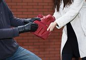 stock photo of yanks  - A thief yanking a red bag from a woman in front of a brick wall - JPG