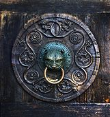 picture of dom  - Antique knocker on a wooden door on facade of Cathedral of St - JPG