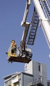 picture of cherry-picker  - color photo image of firefighter lifted in cherry picker - JPG