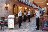 DUBROVNIK, CROATIA - MAY 27, 2014: Waiters standing in front of trattoria Tezoro. Dubrovnik has many restaurants which offer traditional Dalmatian cuisine and some great wine lists.