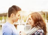 Romantic interracial young couple holding hands and looking at each other outside in sunset light