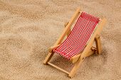 a small deck chair (model) on a sandy beach. symbol photo for vacation, holiday, travel