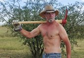 A Shirtless Cowboy Shoulders A Red Pickax