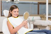 Little girl holding mirror in dentists chair at the dental clinic