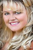 stock photo of plus size model  - headshot portrait of a blonde young adult woman smiling - JPG