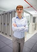 Confident data technician looking at camera in large data center