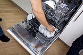 Cropped image of man loading dishwasher in kitchen