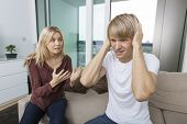 Woman trying to talk as man yells out aloud in living room at home