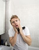 Portrait of man with hairbrush grimacing in bathroom