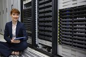 Technician sitting on floor beside server tower using tablet pc in large data center