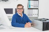Smiling technician sitting at desk in his office