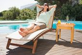 Beautiful young woman relaxing by swimming pool with breakfast on table