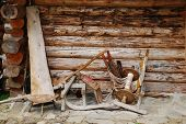 pic of log cabin  - A variety of old wooden farming and weaving objects outside a small wooden log cabin in Bosnia and Herzegovina - JPG