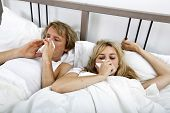 Couple suffering from cold lying on bed